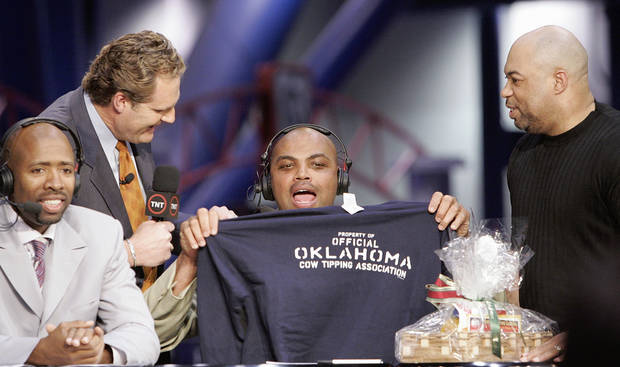 "Charles Barkley holds up an ""Oklahoma Cow Tipping Association"" shirt presented to him by KWTV anchor Kelly Ogle, left, with microphone, and news director Blaise Labbe, right, (cq BLAISE LABBE) on the set of TNT's Inside the NBA at the NBA Jam Session, part of the NBA All-Star events in Houston, Texas, Febraury 16, 2006. Also pictured at right is TNT's Kenny Smith. Barkley has agreed to take up the challenge of Ogle and Labbe to visit Oklahoma. By Nate Billings, The Oklahoman."
