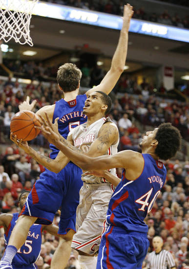 Ohio State's LaQuinton Ross (10) drives between Kansas defenders Jeff Withey (5) and Kevin Young (40) during the first half of an NCAA college basketball game Saturday, Dec. 22, 2012, in Columbus, Ohio. (AP Photo/Mike Munden)