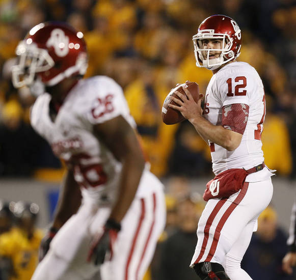 Oklahoma's Landry Jones (12) looks to pass during a college football game between the University of Oklahoma and West Virginia University on Mountaineer Field at Milan Puskar Stadium in Morgantown, W. Va., Nov. 17, 2012. OU won, 50-49. Photo by Nate Billings, The Oklahoman
