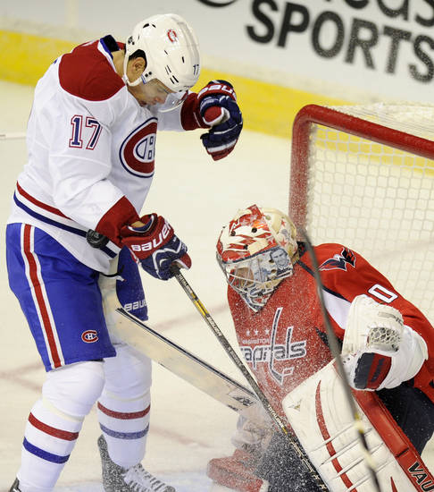 Montreal Canadiens left wing Rene Bourque (17) battles for the puck against Washington Capitals goalie Michal Neuvirth (30), of the Czech Republic, during the first period of an NHL hockey game on Thursday, Jan. 24, 2013, in Washington. (AP Photo/Nick Wass)