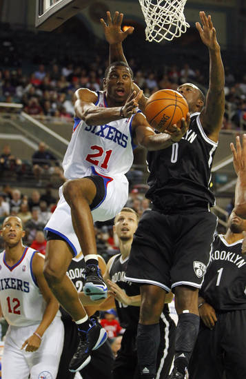 Philadelphia 76ers' Thaddeus Young (21) goes up for a layup as Brooklyn Nets' Andray Blatche (0) defends in the first half during a preseason NBA basketball game, Saturday, Oct. 13, 2012, in Atlantic City, N.J. (AP Photo/Rich Schultz)