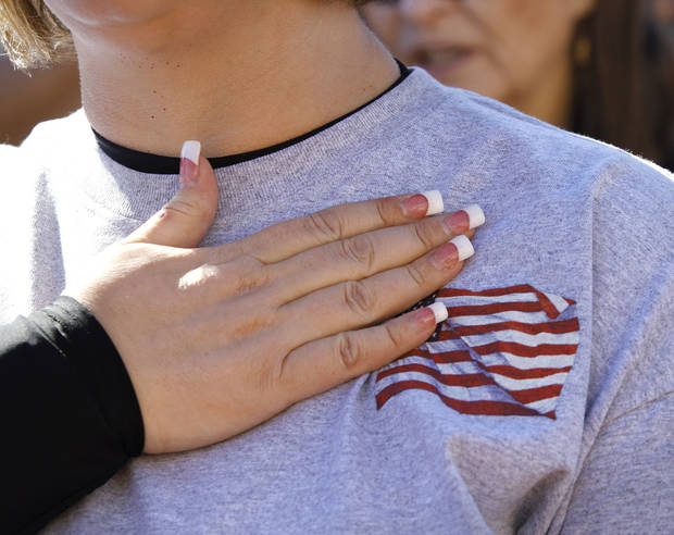 A woman covers her heart while reciting the pledge of allegiance at the start of the rally. Organizers said an estimated 1800 people from throughout Oklahoma crowded into the south plaza at the state Capitol Saturday afternoon, Jan. 19, 2013, to voice their support for their second amendment rights and to express  concerns about proposed gun control legislation being considered by the federal government in the wake of the school shooting in Connecticut last month. Many  held aloft hand-made signs or waved American flags as speakers addressed the gun rights rally.  Photo by Jim Beckel, The Oklahoman