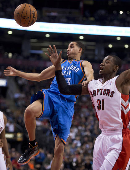 Toronto Raptors guard Terrence Ross (31) knocks the ball loose as he fouls Oklahoma City Thunder guard Kevin Martin during the first half of NBA basketball game action in Toronto on Sunday, Jan. 6, 2013. (AP Photo/The Canadian Press, Frank Gunn)  ORG XMIT: FNG104