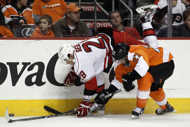 Carolina Hurricanes' Alexander Semin, left, and Philadelphia Flyers' Bruno Gervais dig for the puck along the boards in the first period of an NHL hockey game on Saturday, Feb. 2, 2013, in Philadelphia. (AP Photo/Tom Mihalek)