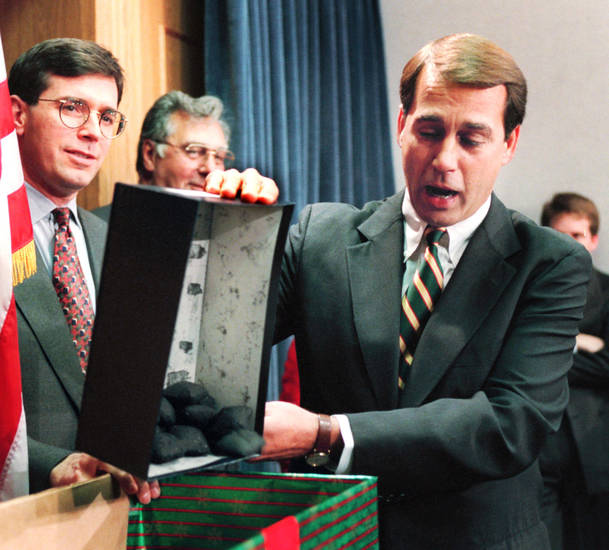 FILE - In this Dec. 21, 1995, file photo Rep. John Boehner, R-Ohio, dumps out coal, his so-called Christmas gift to President Clinton, during a news conference about the federal budget on Capitol Hill as Congressional Republicans tried to restart balanced budget talks on day six of the partial government shutdown. President Barack Obama and his officials are doing their best to drum up public concern over the shock wave of spending cuts that could strike the government in just days. So it�s a good time to be alert for sky-is-falling hype. (AP Photo/Denis Paquin, File)