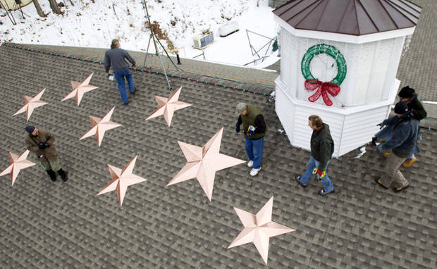 People work on the installation of 26 stars on the roof of the Sandy Hook fire station Tuesday, Jan. 1, 2013, in Newtown, Conn. The stars were made and installed by a group of local contractors, led by Greg Gnandt, to honor the memory of the victims of the Sandy Hook school shooting. (AP Photo/The News-Times, Brett Coomer)