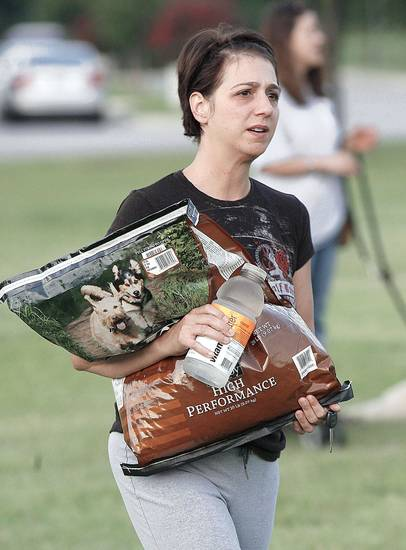 Laura Lorg brings a bag of dog food.