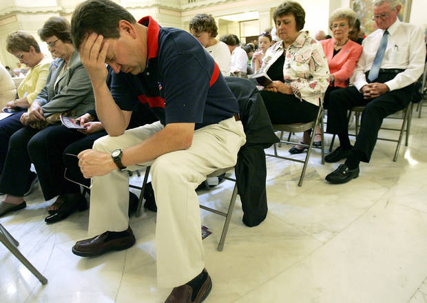 Kevin Kellogg, of Yukon, joins others as he bows his head during a prayer at the 2007 National Day of Prayer services in the Oklahoma state Capitol.   Oklahoman Archive photo <strong>John Clanton - The Oklahoman</strong>