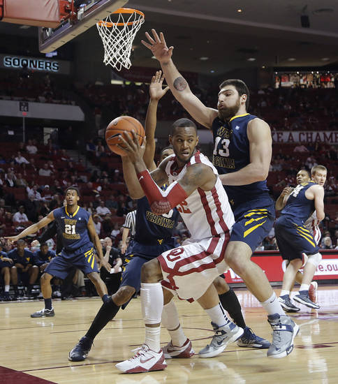 Oklahoma's Amath M'Baye (22) tries to drive past West Virginia 's Deniz Kilicli (13) during the first half of the college basketball game between the University of Oklahoma Sooners (OU) and the West Virginia University Mountaineers (WVU) at the Lloyd Noble Center on Wednesday, March 6, 2013, in Norman, Okla. Photo by Chris Landsberger, The Oklahoman