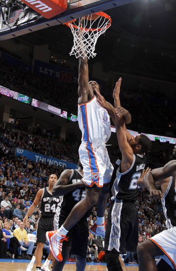 Oklahoma City Thunder&#039;s Serge Ibaka (9) shoots over San Antonio Spurs&#039; Tim Duncan (21) during the the NBA basketball game between the Oklahoma City Thunder and the San Antonio Spurs at the Chesapeake Energy Arena in Oklahoma City, Sunday, Jan. 8, 2012. Photo by Sarah Phipps, The Oklahoman