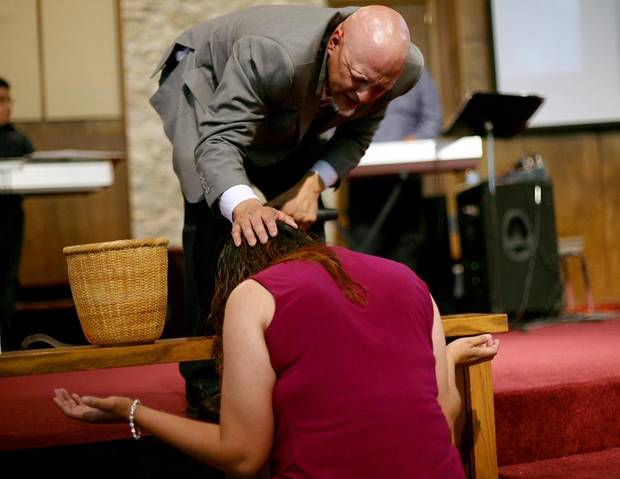 Pastor Eddie Gallegos prays with a member of the congregation at his church in south Oklahoma City. Photo by John Clanton, The Oklahoman