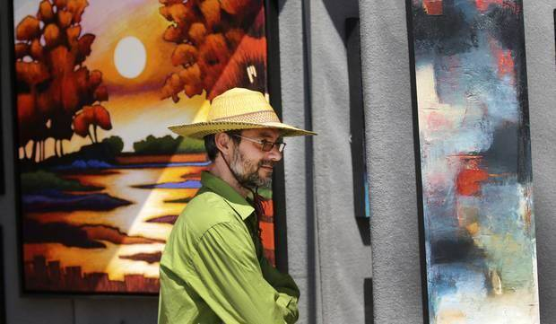 Artist Joachim Knill, Hannibal, Mo., looks at paintings by Albuquerque, N.M., artist Scott Swezy at the 2014 Festival of the Arts in Oklahoma City, Tuesday April 22, 2014. Photo By Steve Gooch, The Oklahoman