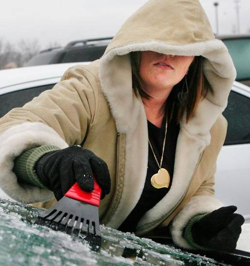 Nikole Edwards scrapes ice from her car windows after she and other employees at Farmer's Insurance  at NW 23 and Villa were released early because of deteriorating weather conditions Monday, Jan. 26, 2009.  BY JIM BECKEL, THE OKLAHOMAN