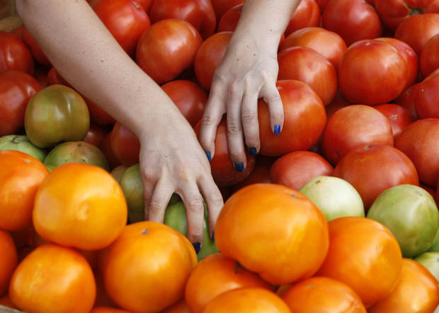 A customer searches through red, green and yellow tomatoes in 2011 at Edmond�s Farmers Market.