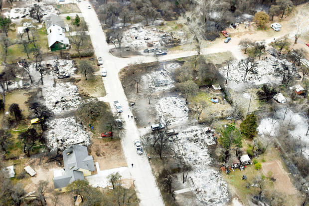 A fire-devastated neighborhood near Hiwassee Road and SE 15 in Choctaw is shown Friday. Scott and Pam Kimbrough, shown at top right, look at the remains of their home at 600 N Henney Road in Choctaw. It was destroyed Thursday in a wildfire. TOP PHOTO BY STEVE GOOCH/BOTTOM PHOTO BY PAUL HELLSTERN, THE OKLAHOMAN