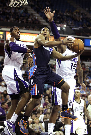 Charlotte Bobcats guard Ramon Sessions, center, drives to the basket between Sacramento Kings' Jason Thompson, left, and DeMarcus Cousins during the first quarter of an NBA basketball game in Sacramento, Calif., Sunday, March 3, 2013. (AP Photo/Rich Pedroncelli)