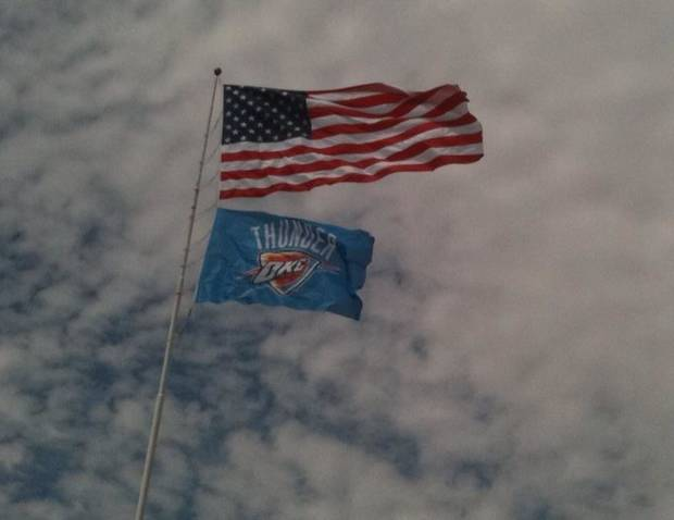 The Oklahoma City Thunder flag flies underneath the U.S. flag today in Bricktown. Photo by Doug Hoke