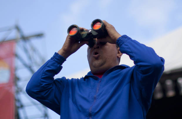 Venezuela's President Hugo Chavez looks at the crowd through binoculars during a campaign rally in Maracay, Venezuela, Wednesday, Oct. 3, 2012. Chavez is running for re-election against opposition candidate Henrique Capriles in presidential elections on Oct . 7. (AP Photo/Rodrigo Abd)