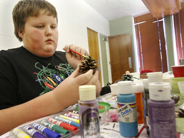 Michael Kowalchyk, 11, of Blanchard, adds color to a pine cone by applying several paints. Children made ornaments to take home or hang on a Christmas tree at Will Rogers Garden Exhibition Center.  PhotoS by Jim Beckel, The Oklahoman