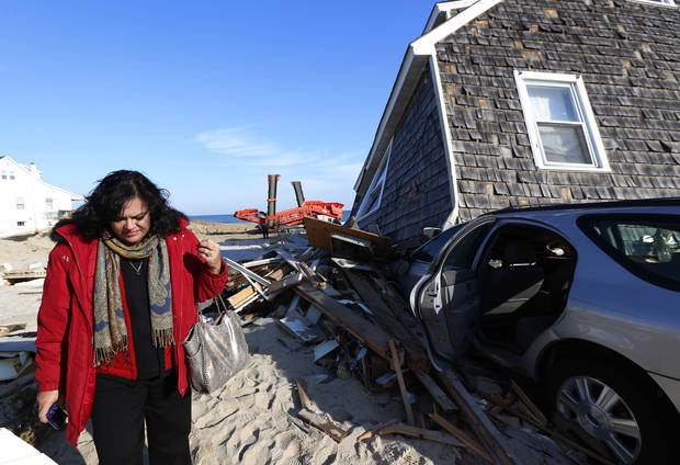 New Jersey State Assemblywoman Marlene Caride walks near a home damage by Superstorm Sandy, Thursday, Nov. 29, 2012, in Normandy Beach, N.J. The New Jersey General Assembly took a tour of areas hit a month after the storm. (AP Photo/Julio Cortez)