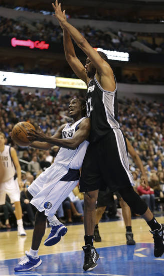 Dallas Mavericks guard Darren Collison, left, goes for a shot against pressure from San Antonio Spurs forward Tim Duncan during the first half of an NBA basketball game in Dallas on Sunday, Dec. 30, 2012. (AP Photo/Mike Fuentes)