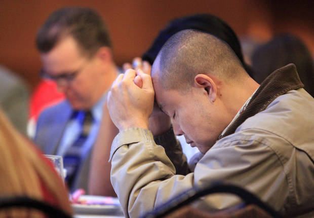 Brad Riebe, right, of Oklahoma City,  bows his head in prayer at the 2011 CBMC Metro Prayer Breakfast in downtown Oklahoma City. The 2013 event is set for March 26 at the Cox Convention Center.   <strong>PAUL B. SOUTHERLAND - PAUL B. SOUTHERLAND</strong>