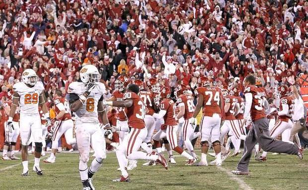 Oklahoma players celebrate in front of Oklahoma States Joe Mitchell, left, and Daytawion Lowe after the Sooners defeated the Cowboys 51-48 in overtime on Saturday. Photo by Sarah Phipps, The Oklahoman