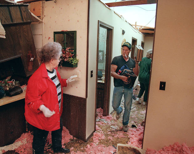 MAY 3, 1999 TORNADO: Tornado victims, damage: Jack Shafer (right) with wife Rhonda, family and friends moves possessions from the roofless part of his house to an area where some roof remained after the Tornado.