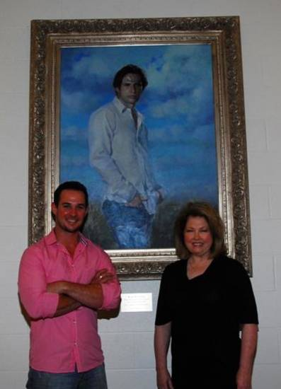 Choctaw-born and bred actor Ryan Merriman and Choctaw artist Kathryn Walker Richarson smile during a reception dedicating the portrait she painted of him to Choctaw High School. The portrait now hangs in the Performing Arts Center of the school, which is Merriman's alma mater. (Photo courtesy Keith Walker and Francesca Kozakowski)