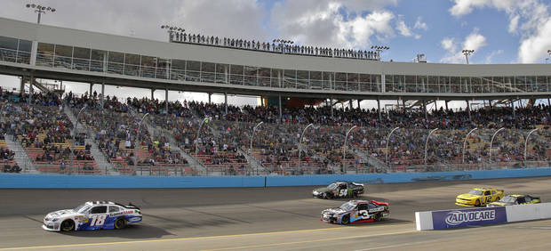 Pole-sitter Joey Logano (18) leads the field out of Turn 1 at the start of the NASCAR Nationwide Series auto race, Saturday, Nov. 10, 2012, at Phoenix International Raceway in Avondale, Ariz. (AP Photo/Matt York)