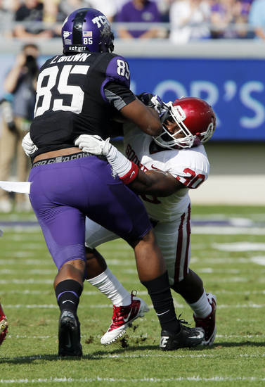 Oklahoma's Javon Harris (30) stops TCU's LaDarius Brown (85) after a catch during the college football game between the University of Oklahoma Sooners (OU) and the Texas Christian University Horned Frogs (TCU) at Amon G. Carter Stadium in Fort Worth, Texas, on Saturday, Dec. 1, 2012. Photo by Steve Sisney, The Oklahoman