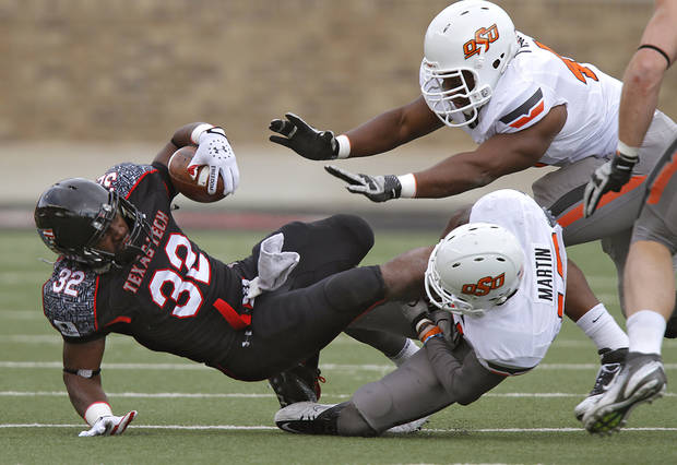 Texas Tech Red Raiders running back Aaron Crawford (32) is brought down by Oklahoma State Cowboys safety Markelle Martin (10) and Tyler Johnson (40) during the college football game between the Oklahoma State University Cowboys (OSU) and Texas Tech University Red Raiders (TTU) at Jones AT&T Stadium on Satruday, Nov. 12, 2011. in Lubbock, Texas.  Photo by Chris Landsberger, The Oklahoman  ORG XMIT: KOD