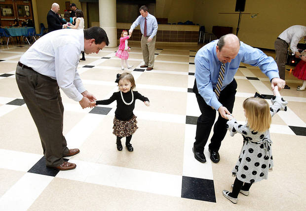 Chris Carrol and his 2-year-old daughter, Maggie, left, and Mike Sheline and his 3-year-old daughter, Brooke, dance during the Deer Creek Daddy Daughter Dance at Deer Creek High School.