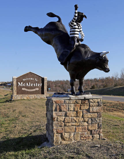 A statue of the Oklahoma State Penitentiary prison rodeo sits in front of a sign welcoming visitors to McAlester, Okla., Wednesday, Dec. 7, 2011. Photo by Nate Billings, The Oklahoman