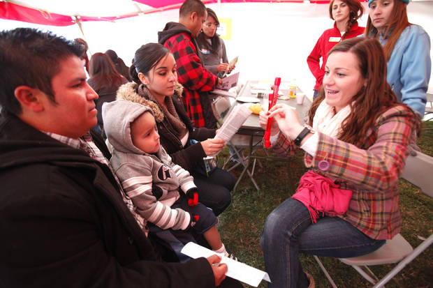 UCO Dietetic intern Megan Shamleffer talks about cholesterol to Javier Ortega, three year old Christopher Ortega, and Sarai Ortega, as LOVE OKC and Convoy of Hope  distributed goods and services to metro residents at the old John Marshall High School in Oklahoma City, OK, Saturday, October 6, 2012. Services included groceries, consultations with health professionals, haircuts, family portraits, job fair, live entertainment and a free lunch for those in need.  By Paul Hellstern, The Oklahoman
