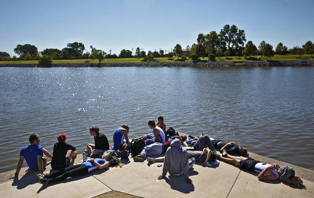 Members of the University of Kansas rowing team relax in the sun as they wait to compete during the Oklahoma Regatta Festival at the Oklahoma River on Saturday, Oct. 1, 2011, in Oklahoma City, Okla. Photo by Chris Landsberger, The Oklahoman 