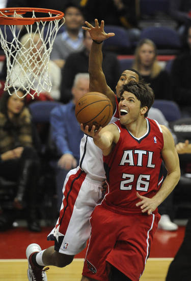 Atlanta Hawks guard Kyle Korver (26) goes up for a basket against the defense of Washington Wizards guard Garrett Temple during the first half of their NBA basketball game on Saturday, Jan. 12, 2013, in Washington. (AP Photo/Richard Lipski)