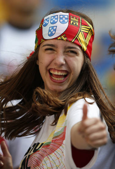 <p>A Portuguese fan wearing the national flag on her head dances on the stands during the Euro 2012 soccer championship Group B match between Denmark and Portugal in Lviv, Ukraine, Wednesday, June 13, 2012. (AP Photo/Armando Franca)</p>