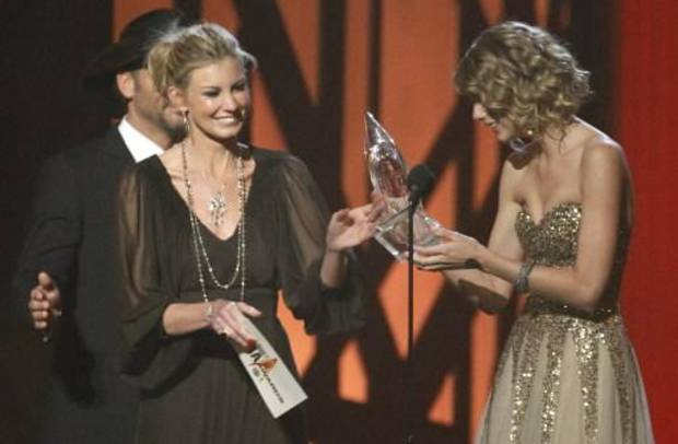 Faith Hill and Tim McGraw present Taylor Swift with the entertainer of the year award at the CMA's. (AP photo by Mark Humphrey)