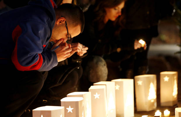 A man reacts placing candles on a makeshift memorial in honor of the victims who died a day earlier when a gunman opened fire in an elementary school, Saturday, Dec. 15, 2012, in Newtown, Conn. The man, who died from a self-inflicted wound, allegedly killed his mother at their home and then opened fire Friday inside the Sandy Hook Elementary school, massacring 26 people, including 20 children. (AP Photo/Julio Cortez) ORG XMIT: CTJC138