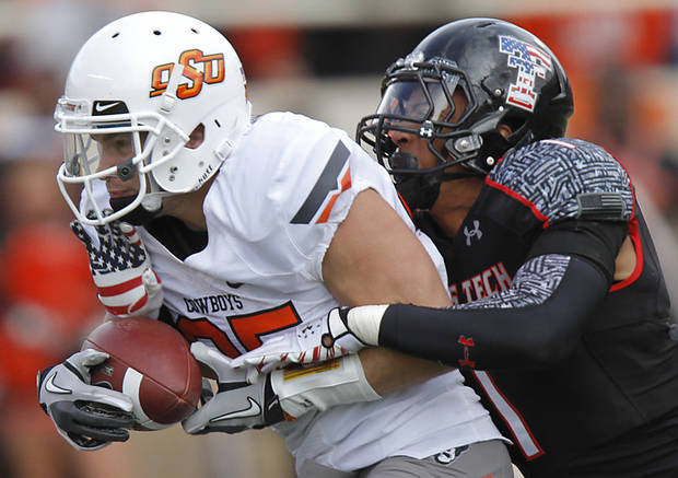 Oklahoma State Cowboys wide receiver Josh Cooper (25) makes a catch in front of Texas Tech Red Raiders safety Terrance Bullitt (1) during the college football game between the Oklahoma State University Cowboys (OSU) and Texas Tech University Red Raiders (TTU) at Jones AT&T Stadium on Saturday, Nov. 12, 2011. in Lubbock, Texas.  Photo by Chris Landsberger, The Oklahoman  ORG XMIT: KOD