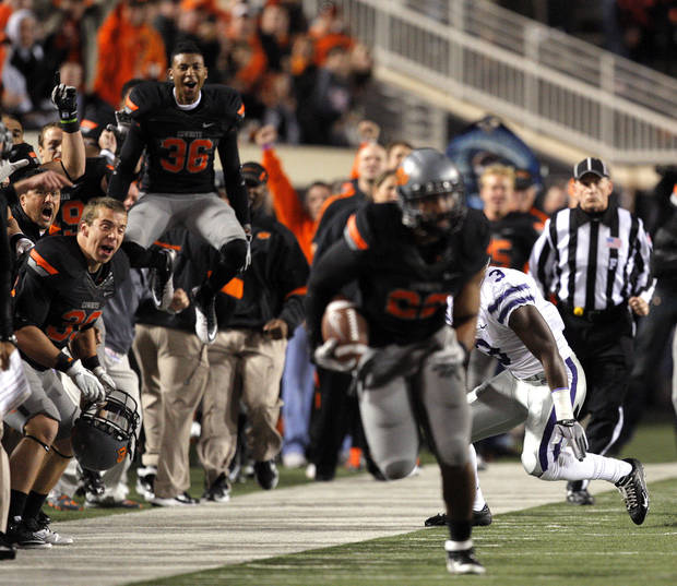 The Oklahoma State sideline cheers as Oklahoma State's James Thomas (22) returns a tipped pass during a college football game between the Oklahoma State University Cowboys (OSU) and the Kansas State University Wildcats (KSU) at Boone Pickens Stadium in Stillwater, Okla., Saturday, Nov. 5, 2011.  Photo by Sarah Phipps, The Oklahoman