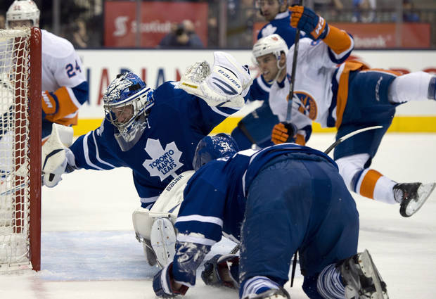New York Islanders center John Tavares, right, flies through the air as his shot gets past Toronto Maple Leafs goaltender James Reimer and defenseman Jake Gardiner, foreground, during first-period NHL hockey game action in Toronto, Thursday, April 18, 2013. (AP Photo/The Canadian Press, Frank Gunn)