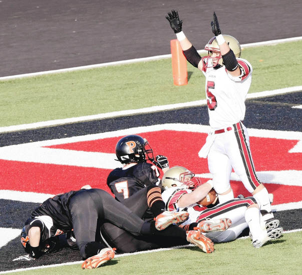 Lincoln Christian's Sam Doerner, top right, gives the touchdown signal after teammate Matt Lawwill scored during the third quarter.  Photo by CORY YOUNG, Tulsa World