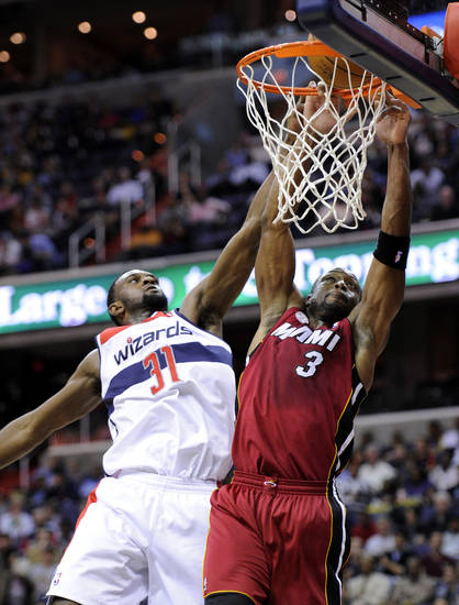 Miami Heat guard Dwyane Wade (3) goes to the basket against Washington Wizards forward Chris Singleton (31) during the first half of an NBA basketball game, Tuesday, Dec. 4, 2012, in Washington. (AP Photo/Nick Wass)