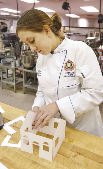 Pastry Arts instructor chef Leslie Davis makes a pattern for gingerbread houses being made by students in the pastry arts kitchen at Platt College in Moore. Their houses will be entered into a gingerbread house contest Dec. 7 that is part of Moore's Christmas in Old Town celebration. PHOTO BY PAUL B. SOUTHERLAND, THE OKLAHOMAN <strong>PAUL B. SOUTHERLAND - PAUL B. SOUTHERLAND</strong>