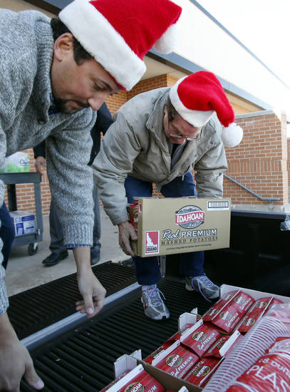 Volunteers Patrick Moore, left, and Bob Magarian unload supplies as they get ready for the Norman Christmas Day Community Dinner.  PHOTO BY STEVE SISNEY, THE OKLAHOMAN