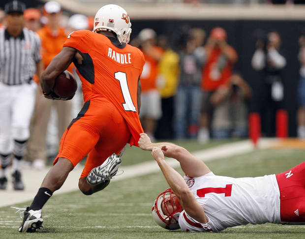 OSU's Joseph Randle slips past Nebraska's Adi Kunatic during the college football game between the Oklahoma State Cowboys (OSU) and the Nebraska Huskers (NU) at Boone Pickens Stadium in Stillwater, Okla., Saturday, Oct. 23, 2010. Photo by Sarah Phipps, The Oklahoman
