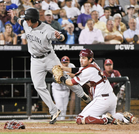 South Carolina's LB Dantzler, left, is tagged out at home plate by Arkansas catcher Jake Wise after South Carolina's Erik Payne reached first base on a fielder's choice in the sixth inning of an NCAA College World Series baseball game in Omaha, Neb., Thursday, June 21, 2012. (AP Photo/Ted Kirk)