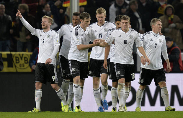 Germany's Andre Schuerrle, left, celebrates with his teammates after scoring their side's second goal during the 2014 World Cup Group C  qualifying soccer match between Germany and Ireland in Cologne, Germany, Friday, Oct. 11, 2013. (AP Photo/Martin Meissner)